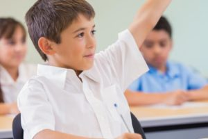 Elementary age Hispanic little boy is student in private elementary school. He is raising his hand to ask or answer a question during class. School children are wearing white and blue private school uniforms.