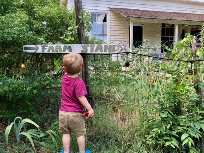 child near farm stand sign at Boggy Creek Farms in Austin, Texas