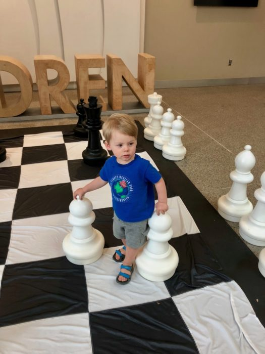 child playing on giant chess board at Austin Central Library