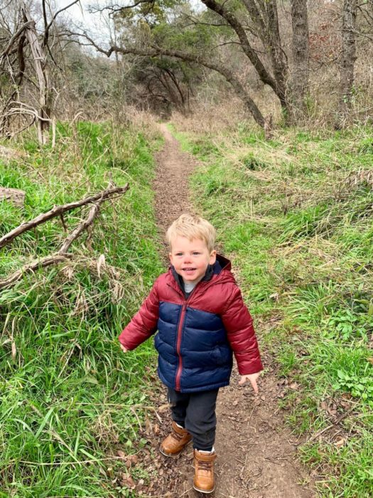 boy walking on a trail on the Barton Creek Greenbelt at Free Forest School in Austin, Texa