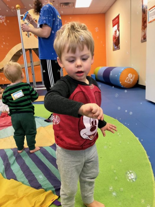 boy playing with bubbles at gymboree in austin, texas
