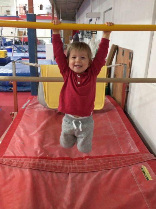 boy swinging on bars at gymnastics class at Crenshaw Athletic Club in Austin, Texas