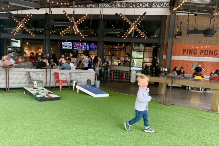 little boy running on the lawn at culinary dropout restaurant at the domain in austin, texas