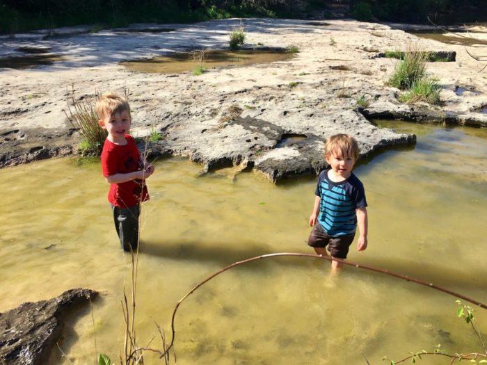 two children playing in Barton Creek in Austin, Texas