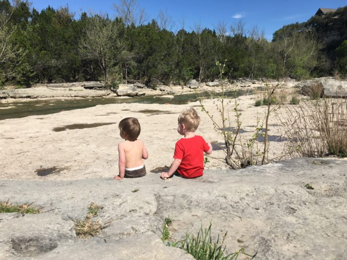 two toddlers sitting on a large rock overlooking a creek