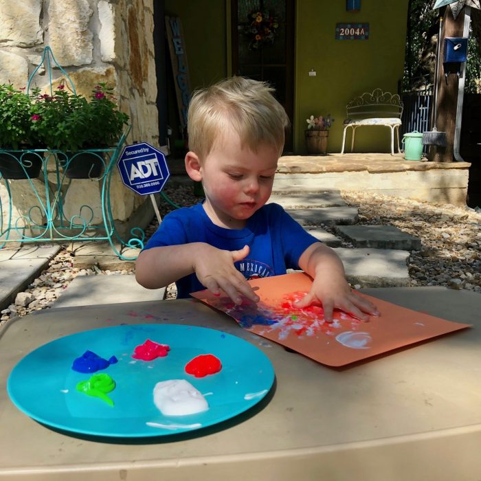 toddler boy fingerpainting in backyard