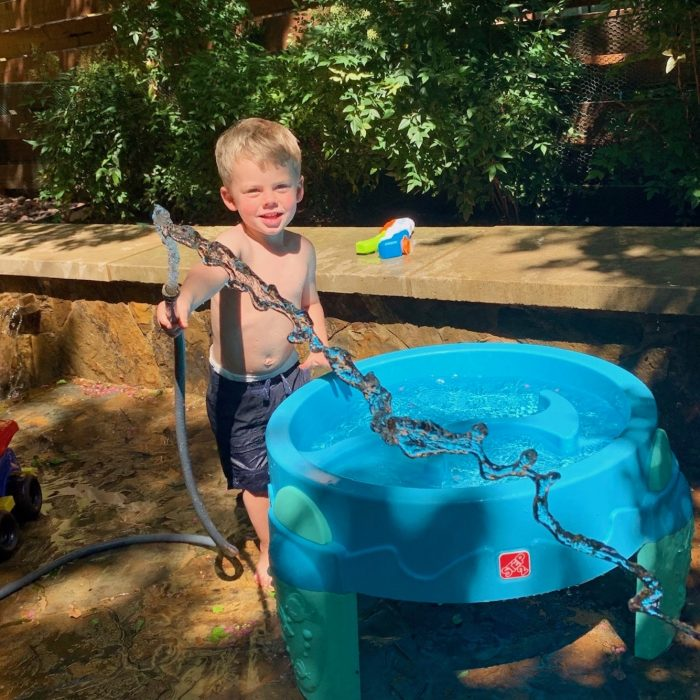 boy playing with hose and water table in backyard