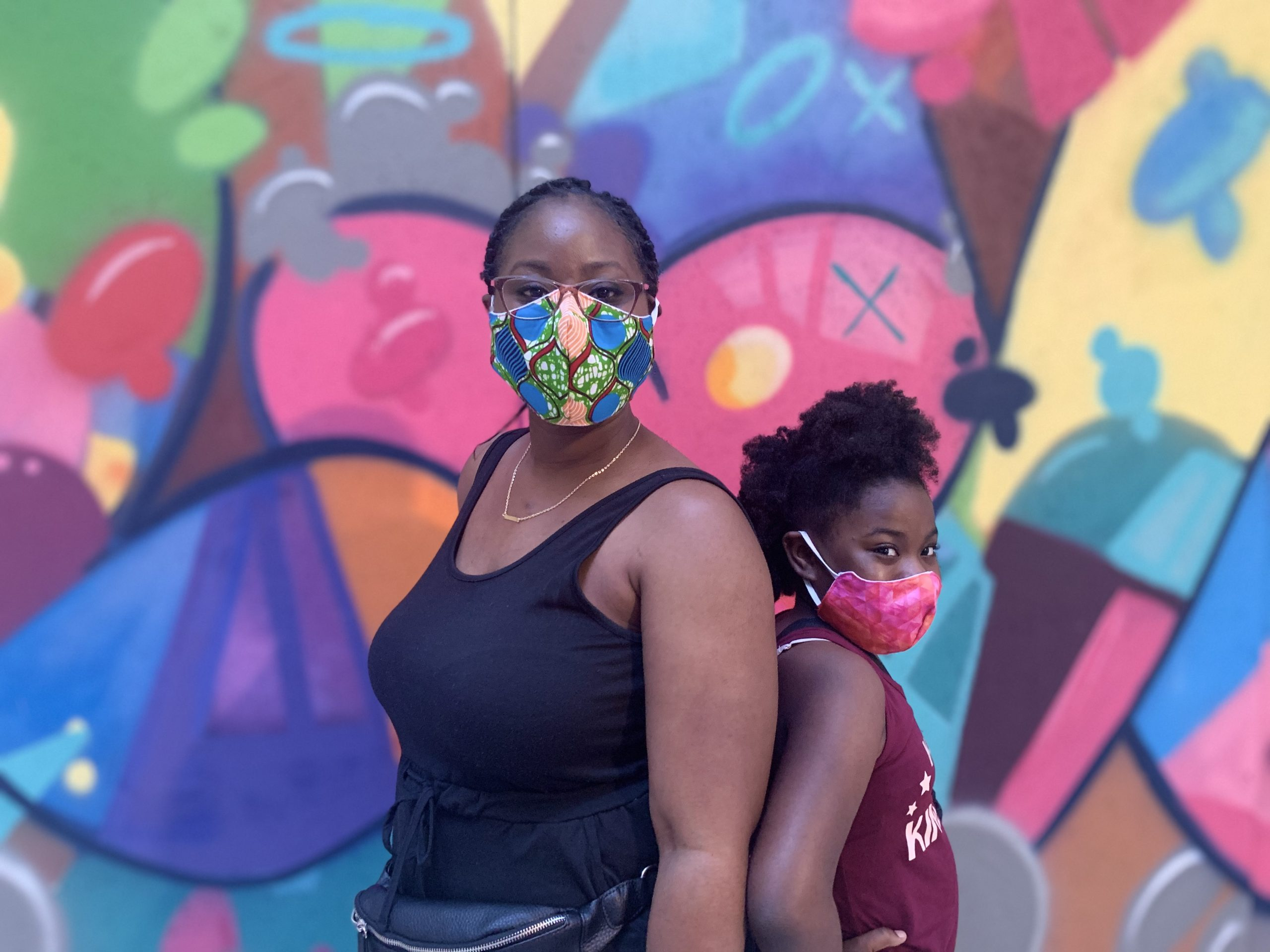 mother and daughter posing in front of mural